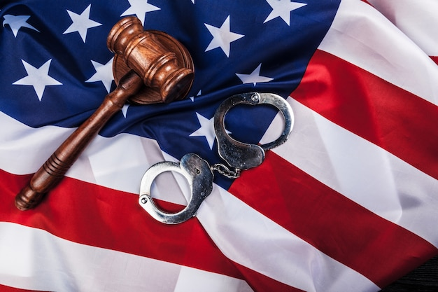 Martelletto, manette e bandiera americana su legno.
