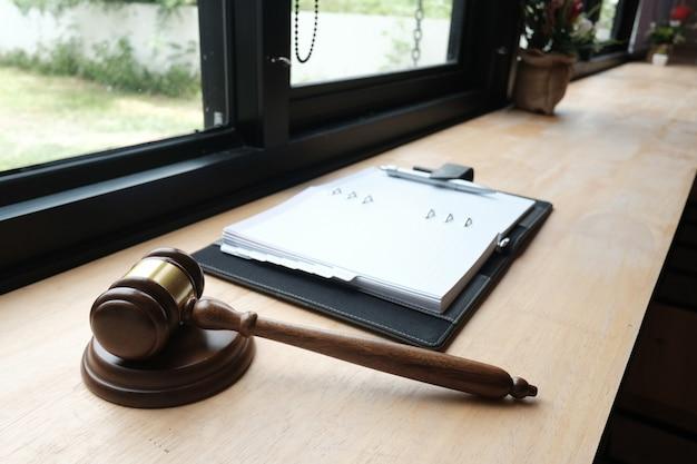 Martelletto & taccuino di legge legale sulla tavola di legno.