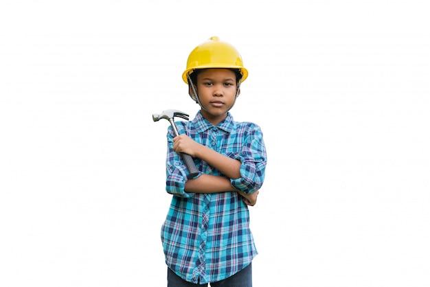 Martello afroamericano della tenuta del ragazzo che indossa un casco di sicurezza giallo su fondo bianco