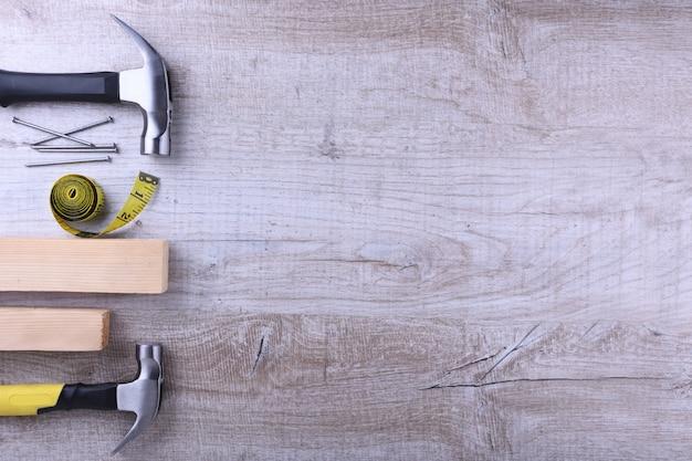 Martello di ferro, nastro di centimetro e chiodi sul tavolo di legno