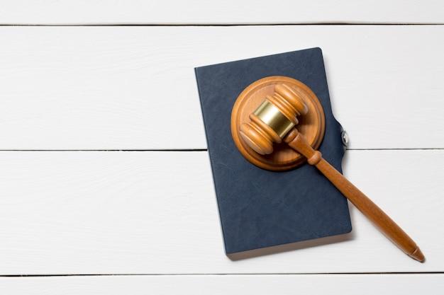 Martello di legno del martelletto del giudice con un libro sul fondo di legno bianco della tavola.