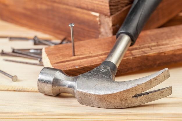 Martello e chiodi su fondo di legno