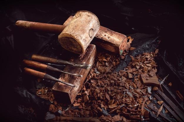 Martello e scalpelli in legno su segatura, strumenti di scultura in legno su sfondo scuro