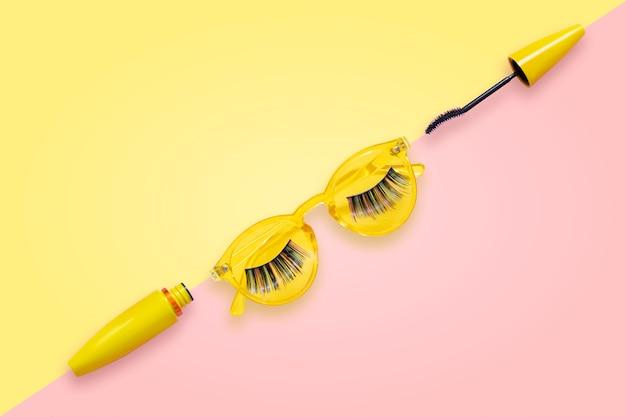 Mascara in tubo giallo con pennello aperto su occhiali da sole rosa e gialli con ciglia finte.