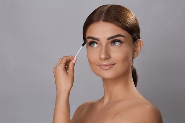 Mascara. trucco di bellezza, pelle fresca e morbida e ciglia lunghe e nere che applicano mascara con pennello cosmetico. estensioni delle ciglia. ciglia finte.