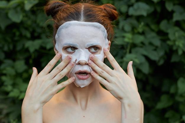 Maschera antietà ritratto di una ragazza tocca il viso con le mani e guarda a lato la pelle chiara
