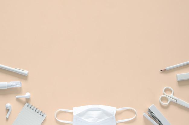 Maschera bianca con materiale scolastico e cancelleria per ufficio per il ritorno a scuola e nuovo concetto normale.