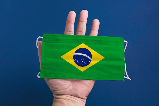 Maschera chirurgica su sfondo blu con bandiera brasiliana - man mano che regge