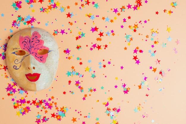 Maschera colorata sul tavolo con coriandoli