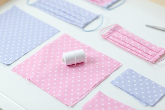 Maschera contro virus fatti a mano, cucire maschera protettiva, pezzi di stoffa punteggiata, fili sul tavolo bianco. piatto disteso con stoffa rosa e blu, forbici e fili.