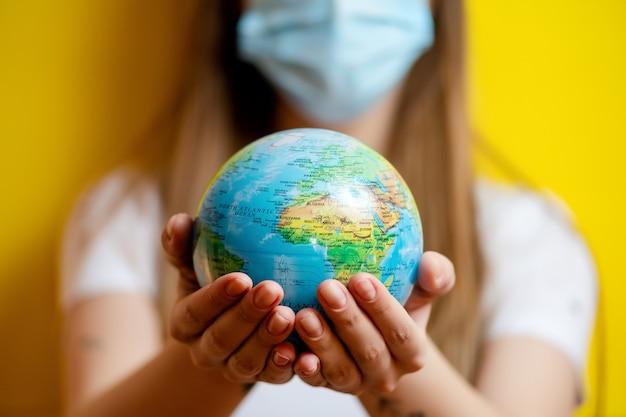 Maschera d'uso del globo del pianeta terra della tenuta della donna