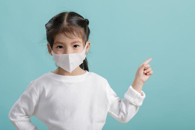 Maschera d'uso del respiratore della ragazza asiatica del piccolo bambino per proteggere lo scoppio del coronavirus e indicare mano il copyspace in bianco