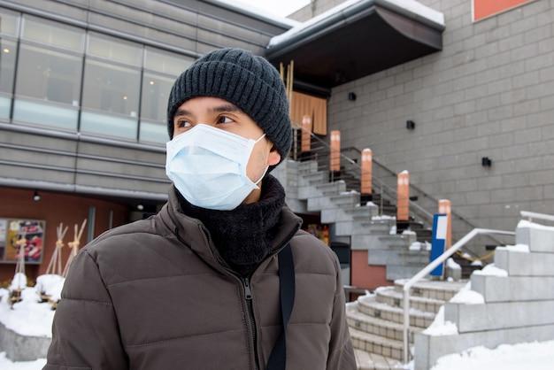 Maschera d'uso dell'uomo turistico asiatico che protegge coronavirus durante l'inverno nel giappone