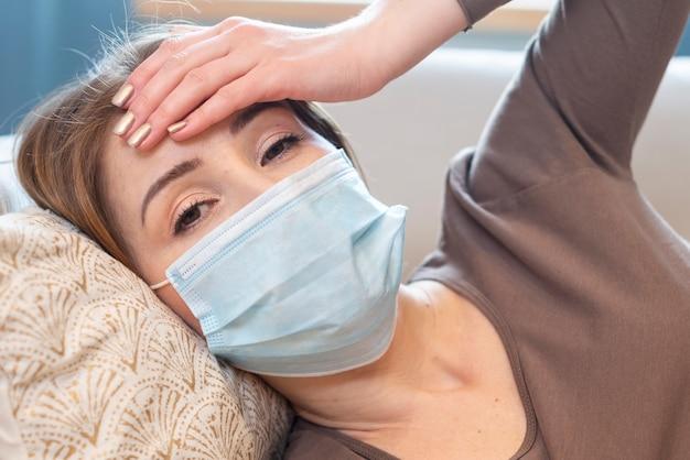 Maschera d'uso della donna del primo piano e avere mal di testa
