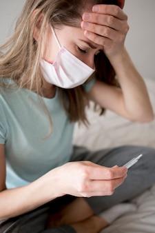 Maschera d'uso della donna dentro che controlla la sua temperatura