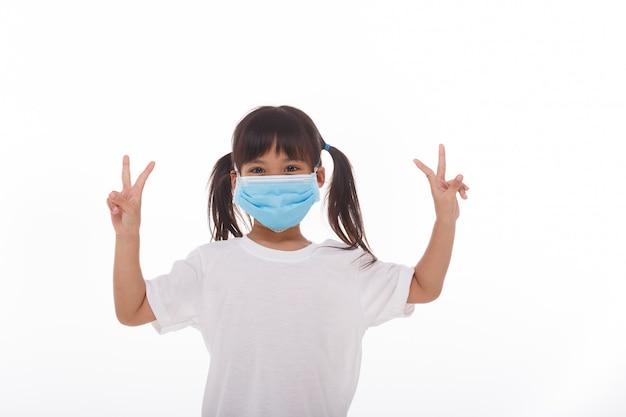 Maschera d'uso della piccola ragazza asiatica che si tiene per mano su con due dita