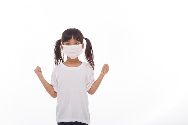 Maschera d'uso della ragazza dell'asia sulla parete bianca