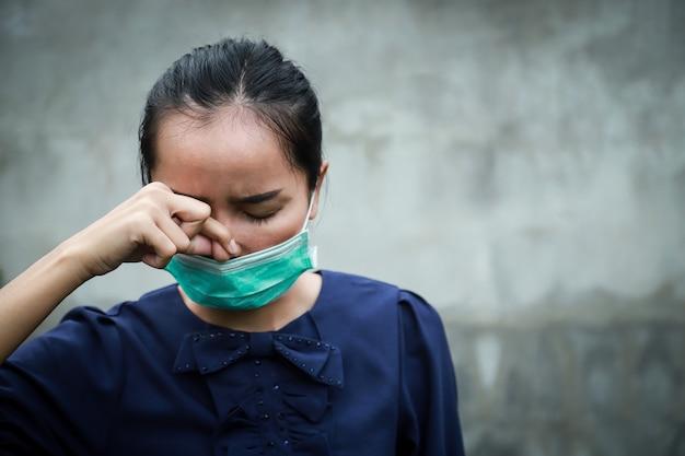 Maschera d'uso di protezione della ragazza asiatica con la sensazione di febbre fredda della malattia per il concetto del virus di corona