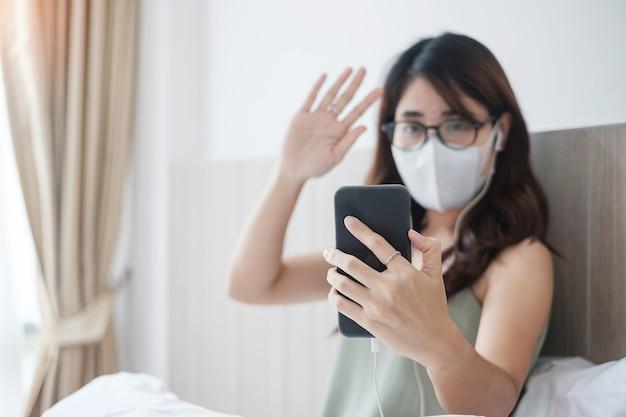 Maschera d'uso e videochiamata della donna di malattia casuale che chiamano dallo smartphone a casa, femmina asiatica che usando incontro app online sul letto. distanza sociale, nuova normalità, lavoro da casa, concetto a distanza e tecnologia
