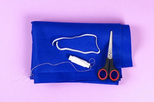 Maschera da notte in feltro blu fai-da-te con filo bianco ricamato