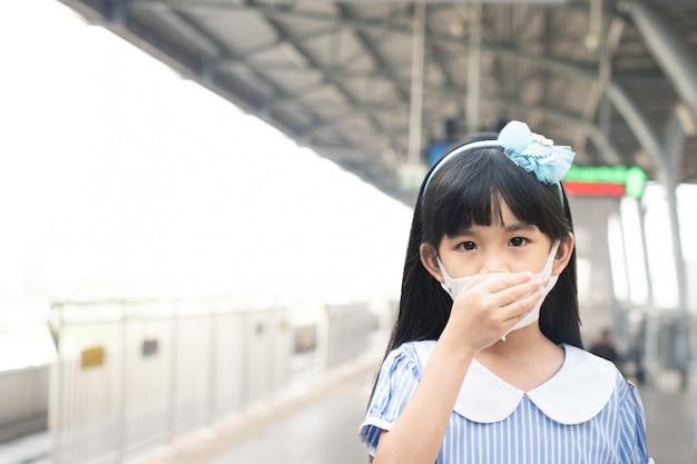 Maschera da portare asiatica della ragazza piccola per prevenire l'infezione da covid-19 o coronavirus alla stazione ferroviaria.