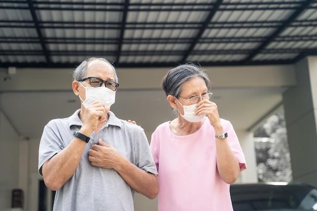 Maschera da portare delle coppie senior anziane asiatiche per prevenire crepuscolo pm 2,5 cattivo inquinamento atmosferico.