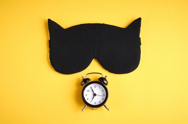 Maschera da sonno nera con orologio su composizione gialla, maschera da gatto con orecchie