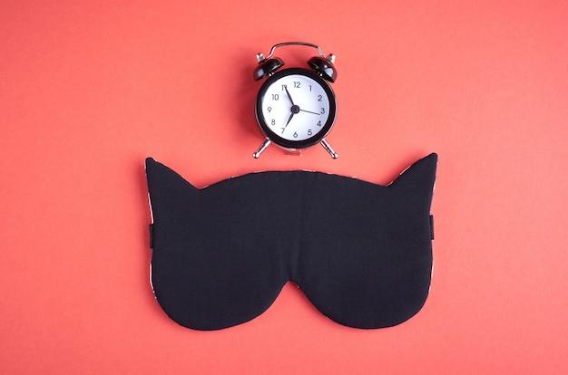 Maschera da sonno nera con orologio su composizione rosa, maschera da gatto con orecchie