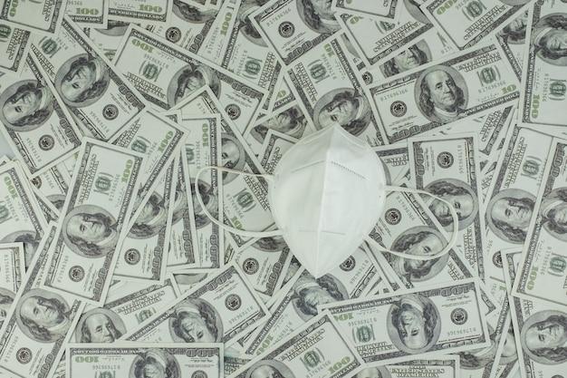 Maschera del dottore medical per la protezione da virus e denaro una pila di banconote da 100 dollari americani un sacco di sfondo