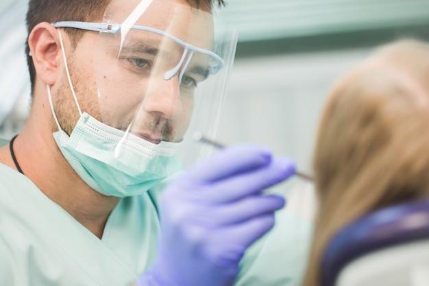 Maschera del primo piano della giovane donna che si siede nella sedia del dentista con la bocca aperta all'ufficio del dentista mentre avendo esame.