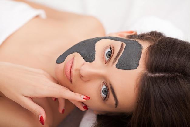 Maschera del primo piano di giovane donna adorabile con la maschera crema in un salone di bellezza.