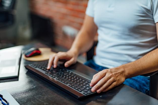 Maschera del primo piano di un uomo di affari che per mezzo della tastiera di computer