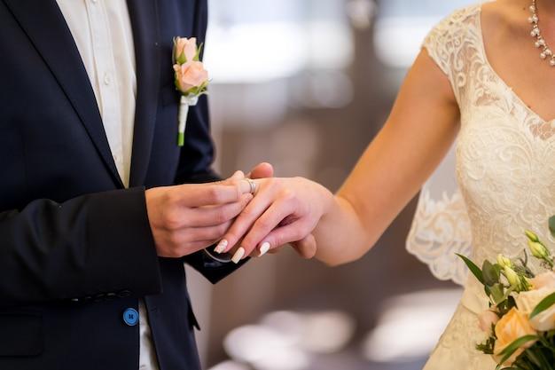 Maschera dell'uomo e della donna con gli anelli di cerimonia nuziale. primo piano delle mani.