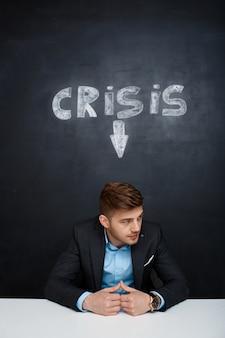 Maschera dell'uomo stanco sopra la lavagna con l'iscrizione di crisi