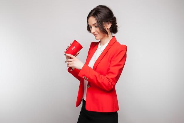 Maschera della donna attraente in vestito rosso con la tazza di birra in mani