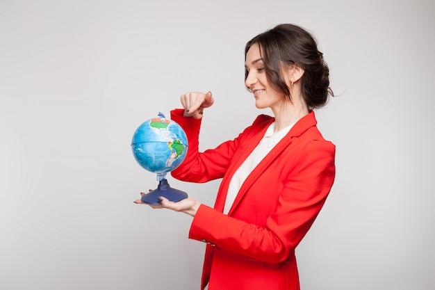 Maschera della donna graziosa in giacca rossa con la sfera della terra in mani