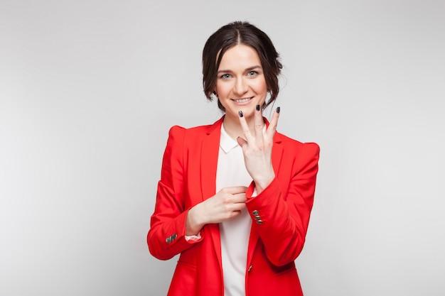 Maschera della donna graziosa in giacca sportiva rossa che mostra i segni