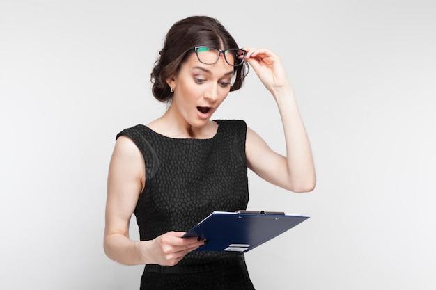 Maschera della donna graziosa in vestito nero con la compressa in mani