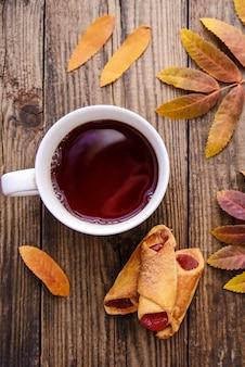 Maschera di autunno delle foglie gialle, una tazza di tè, una sciarpa e un pezzo di carta con la penna su fondo di legno con i biscotti