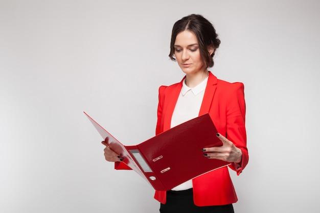 Maschera di bella donna in giacca rossa che sta con i documenti in mani