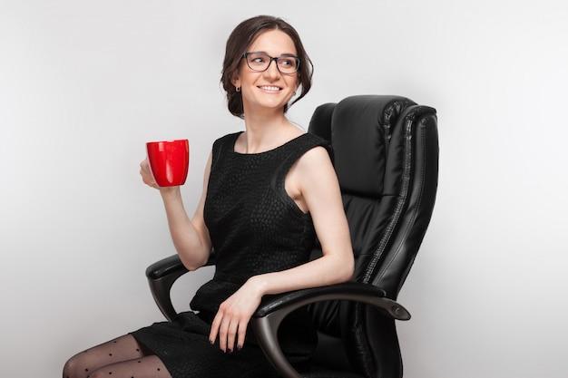 Maschera di bella donna in vestito nero che si siede nella poltrona con caffè in mani
