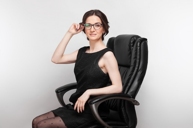 Maschera di bella donna in vestito nero che si siede su una poltrona