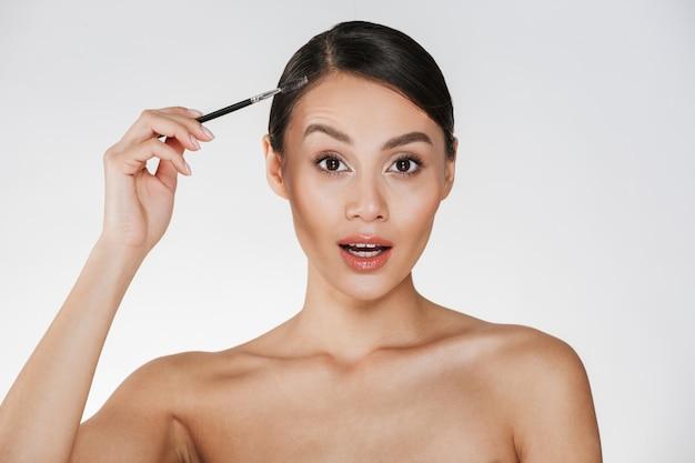 Maschera di bellezza della donna splendida con capelli in panino che osserva sulla macchina fotografica e che tiene spazzola per le sopracciglia, isolata sopra bianco