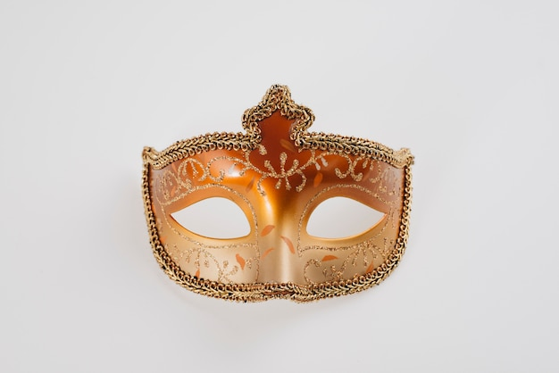 Maschera di carnevale arancione sul tavolo bianco