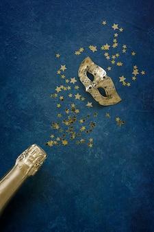 Maschera di carnevale, bottiglia di champagne e coriandoli glitter oro