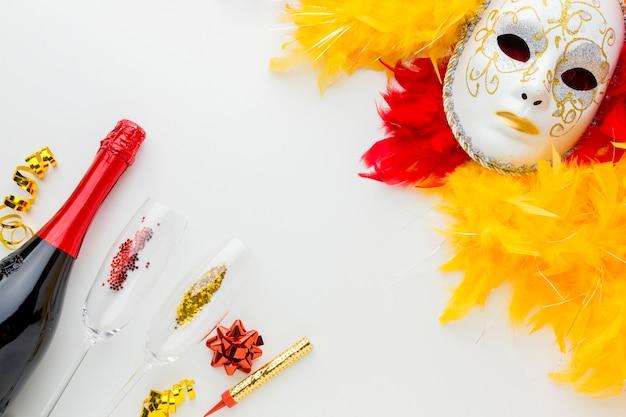 Maschera di carnevale con piume e champagne