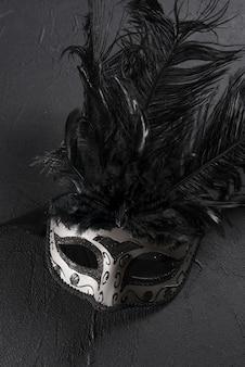 Maschera di carnevale grigio con piuma sul tavolo