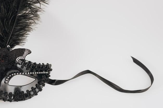 Maschera di carnevale nero con piuma sul tavolo luminoso