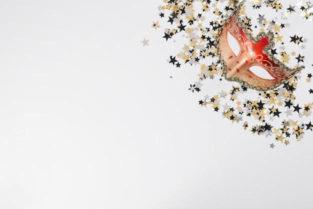 Maschera di carnevale rosso con lustrini sul tavolo