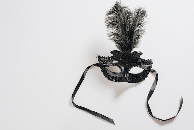 Maschera di carnevale scuro con piuma sul tavolo